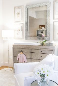 arielle charnas' nursery reveal. featuring our marcelle wide dresser & topper, 18th c. venetian cut-glass mirror, nathalie crystal floor lamp,  pressed botanical art and shelter swivel glider.