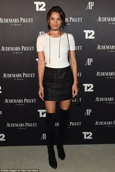 Details: A skin-tight white shirt hugged the swimsuit model's petite upper frame, teamed with a lace-up black mini skirt and thigh-high boots that accentuated her lean legs