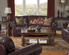 A rich dark brown leather living room set with coffee and end tables. Brown And Blue Living Room, Brown Couch Living Room, Cozy Living Rooms, Living Room Paint, My Living Room, Living Room Decor, Red Curtains Living Room, Leather Living Room Set, Leather Living Room Furniture