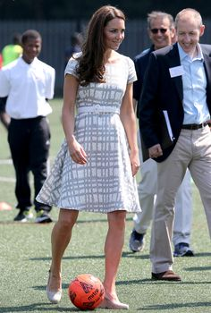Catherine, Duchess of Cambridge kicks a football on the football pitch as she visits Bacon's College on July 26, 2012 in London, England.