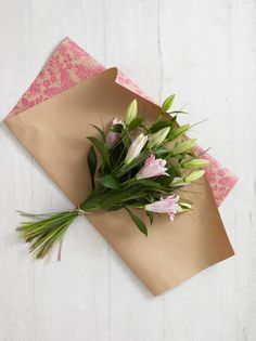 It's always best to wrap a hand-tied bouquet before you give it to someone as a gift. The wrapping paper helps to protect delicate petals in transit, and a well-wrapped bouquet makes a much more pleasing present.