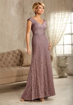 This figure-flattering bodice has a pleated wrap design that features a V-neckline and back, with slight cap sleeves in iridescent chiffon. The waistline is beaded, and the skirt is a semi-A line in matching lace with scattered beading.                                                                                                                   Available in Wisteria, Champagne and Navy.