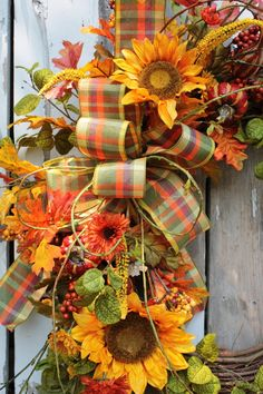 This is a great late summer, early fall wreath. Pleanty of greens and happy sunflowers, sprinkled with pumpkins and berries and tied with a plaid bow. Finished size is 24-26. Thanks for looking