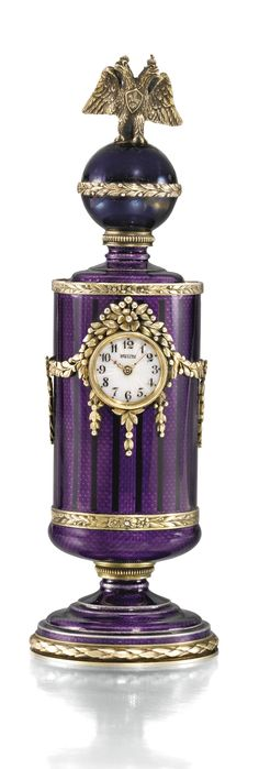 A SILVER-GILT AND ENAMEL TIMEPIECE, BRITZEN, ST PETERSBURG, 1908-1917 cylindrical, standing on a waisted socle, the surface enamelled overall in black-lined and translucent deep purple over wavy prismatic engine turning and mounted with silver-gilt festoons, margents and borders of fructed laurel, the dial with Arabic chapters enamelled in translucent white over moiré engine-turning, the finial with double-headed eagle, 84 standard height 17cm, 6 3/4 in.