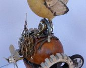 Available on my #ETSY store (until sold) is this lovely #Steampunk art! Wren Racer #5: bird on antique wooden exercise dumbbell mounted on a handmade wood stand, has two handmade wood spoke style wheels with spinner hubcaps, a handmade wheel with rounded spokes at back, handmade propeller with spinner mounted in front with watch and clock parts, bird is wearing a bucket hat with beanie cap, watch part wings and tail had watch movement with a clock spring.