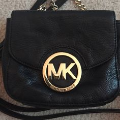 Michael kors black leather cross body This is a great little cross body bag, perfect for concerts and other outings! There are a couple scratches on the MK emblem but they aren't noticeable unless you're looking really close. There's also a small intention in the top left corner of the bag that's shown in the first picture, but it's also not noticeable unless you're looking for it. There's a pocket on the inside and a pocket on the back. Magnetic closure with a leather/chain long strap…