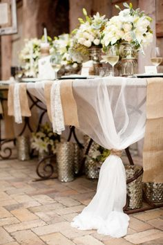 Sheer fabric tied at opposite corners, with burlap runners and lace napkins. Head table ?