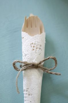 wrap disposable wedding silverware with a paper doily and twine...(cute!...and again,I volunteer!)