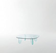 DRAWN TABLE design Naoto Fukasawa | Low and shaped table with feet in transparent glass mm. 19 thick, which are thermowelded to the transparent glass top mm.12 thick, tempered. The rounded shape gives the glass a pleasant and unusual soft dynamic look.