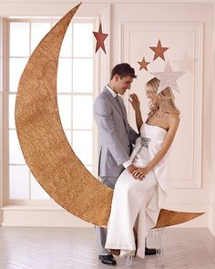 Crescent-moon and star designs shone during the twenties and thirties; channel that era's easy glamour with this photo backdrop. To make, cut foam board into a crescent shape, spray with glue, blanket with glitter, then hang with fishing wire.