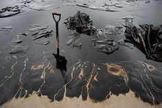 A shovel sits in oil-covered sand at Ao Phrao beach. Volunteers were attempting to clean up the area after a major oil slick hit the island of Ko Samet, Thailand. Environmentalists accused a Thai energy firm of understating the extent of the pipeline leak