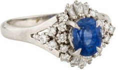 Platinum cocktail ring featuring prong set oval sapphire at center with round brilliant and baguette cut diamond halo.