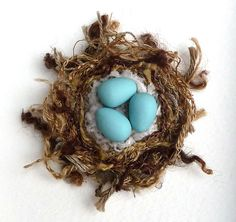 "Fibre nest with polymer clay eggs. The yarns and threads are sewn by hand and with a sewing machine.   approx. 2 ¼"" across"