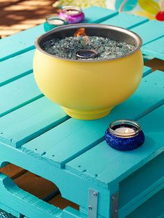 DIY firebowl - Start with a fireproof container, such as this galvanized bowl that we primed and coated with outdoor paint in a cheery hue. Fill the bowl with recycled tempered glass chips, and tuck in a can of alcohol-free gel fuel. With a click of a lighter, the flame will dance and enchant for hours.