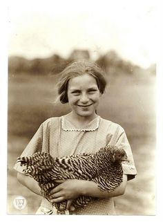 Vintage photo of farm girl with prized chicken.