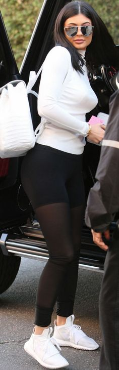 Who made Kylie Jenner's white backpack, long sleeve top, black mesh leggings, white sneakers, and sunglasses?