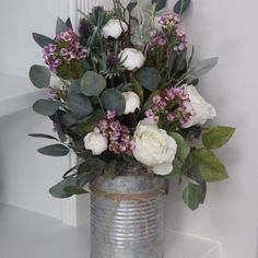 Eucalyptus, mini peonies and roses make this arrangement a perfect piece for spring.