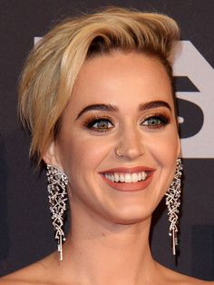 Katy Perry with quinoa in stuck in her teeth and a gold Nike Swoosh teeth jewelry on her left premolar.