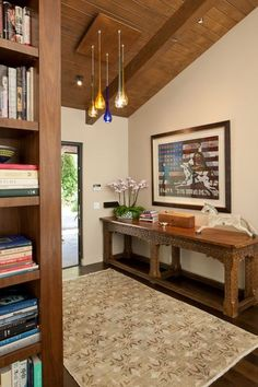 AFTER: A wood shelving unit and walnut floors now warm the space up. The rug and all-wood monk's table belonged to the author's mother. The table once was longer, but Jay had an artisan cut it down, then built the wall long enough to contain it.