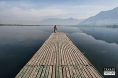 Double-dose of delight - A boatman takes in the tranquil sunrise over the Dal lake in Srinagar.