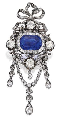 Gold, Silver, Sapphire and Diamond Brooch. Centring a buff-top emerald-cut…