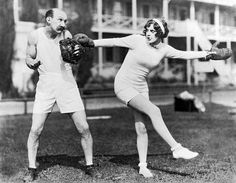 Comedian Jimmy Finlayson questions actress Martha Sleeper's choice of sporting equipment when he invites her for some preseason baseball practice, Hollywood, California, circa 1929. (