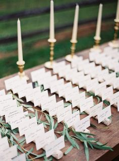 escort cards displayed on birch tree branches. Brass candle sticks and greenery accents.