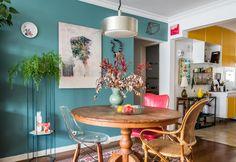Sala de jantar com mesa de madeira redonda tem parede azul turquesa com obras de arte e plantas em suporte vertical alto.