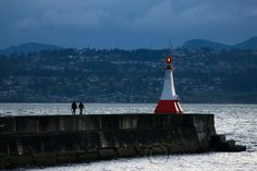 A couple walks along the Victoria harbour's Ogden Point breakwater in Victoria, BC