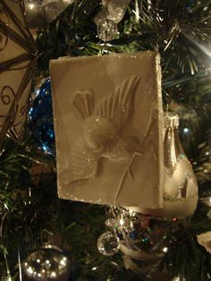 """Paper Clay Springerlie Ornament.  Springerlies are brittle anise-flavored cookies stamped with a cookie mold.  I found a variety of reproduction molds at House on the Hill including this bird. Paper clay is available at Hobby Lobby & online. Roll out the clay between waxed paper to about 1/2"""". Spray mold with PAM and press into clay and remove. Trim edges and insert screw eyes into top and bottom.  Allow to dry then add glitter and crystal drop."""
