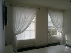 Sheer voiles are mounted over functional roller blinds. A single curtain is swept to one side of each window. They add softness and subtle detail to an otherwise simple window treatment.