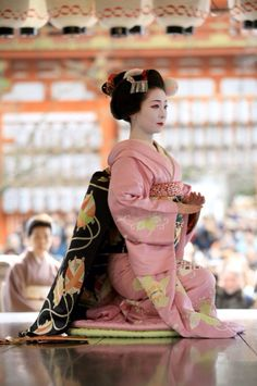 This picture represents a classic image of a Geisha dressed for an average working evening. Note that she is clad from throat to feet in thick padded robes that reveal nothing. Her face is hidden behind a thick cosmetic masks that reveals nothing beyond a serene and classic beauty. A Geisha could assume this posture for hours if need be. Parade rest, as it were. The true Geisha was a Consummate Professional Hostess and Entertainer, not a sexual object.