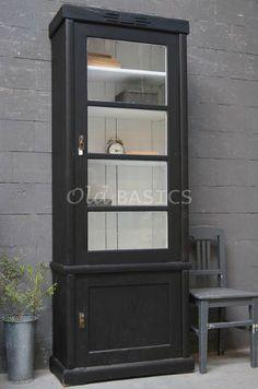 Vitrinekast 10155 - Oude houten kast met een strakke vormgeving. De zwarte kast is achter de vitrine deur wit van kleur, met vier vaste legplanken. Op de koof zit een subtiel hout snijwerkje.