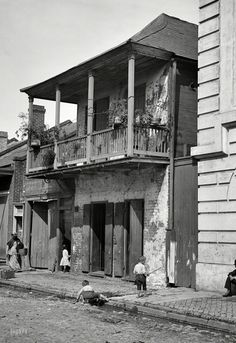 """Street in the French Quarter. Take care not to trip on the guttersnipes."" New Orleans, circa 1880s-1890s."