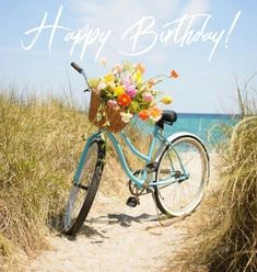 Birthday wishes picture with aqua colored bike, basket of flowers near water. #beachpictureshappybirthday