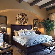 Elegant and cozy; love the arched nook with built in lighting  for the bed, and the high, beamed ceilings