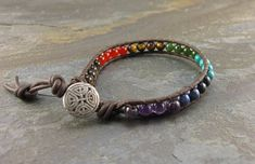 A very casual, leather braided bracelet that's thicker and beefier for men, with the Chakra balancing stones of Smoky Quartz, Carnelian, Tiger Eye, Jade, Turquoise, Dumortierite and Amethyst. Wear your bracelet with positive intentions and the electromagnetic energies of the stones will assist you in developing strength and manifestation of their properties.  New button-Tree of Life!
