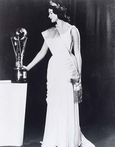 Miss Australia 1956, June Finlayson standing and looking at the Miss Australia trophy