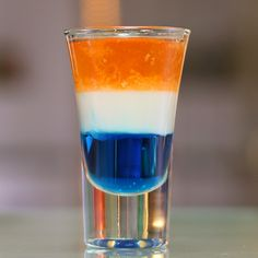 TIDE POD SHOT 1 Part Blue Curacao 1 Part White Chocolate Liqueur 1 Part Orange Vodka PREPARATION 1. Pour blue curacao 1/3 of the way into a shot glass. 2. Using the back of a bar spoon, layer white chocolate liqueur on top, followed by orange vodka. DRINK RESPONSIBLY!