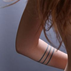 Little armband tattoo of three stripes.
