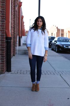 white sweater layered over denim button-up, jeans, suede wedges
