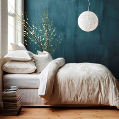 Minimalist decor with a great-looking teal wall. I just love those paper lamps for some reason.