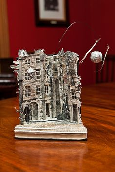 """Paper Sculpture """"A wonderfully atmospheric street scene with what appears to be a silvery moon with wisps of cloud hanging from it. There are even goings-on visible behind some of the windows… """""""