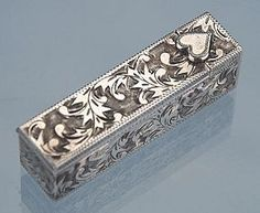 "vintage Japanese ""950"" Sterling silver lipstick case, with finely etched scrolling leaf designs on all four sides and the top."