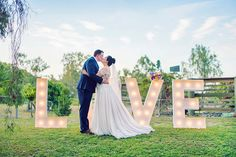 Bride and groom photo idea with LOVE letter lights at a country wedding | Madelyn Holmes Photographics