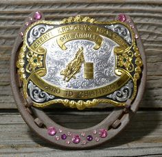 Trophy buckle display. Maybe with the horse shoe of the horse he won with
