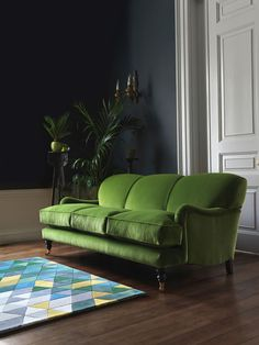 How to use Pantone's Colour of the Year for 2017, Greenery, in your living room: A piece of furniture is a great option in an on trend colour. In this room it's the focal point and it works because the walls are plain and painted in a deep gunmetal grey which adds the perfect backdrop. A bright geometric rug introduces new colours to the space with the odd Greenery shade keeping the look cohesive. Vases and botanical plants will carry through the look. Find more ideas at housebeautiful.co.uk