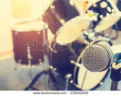 Microphone in a recording studio or concert hall with drum in out of focus background.  : Vintage style and filtered process. - stock photo