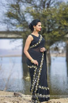 Featuring the Black Buttercup saree in pitch black, 100% pure silk georgette with white ribbonwork buttercup flowers and golden thread embroidery leaves, that is perfect for evening affairs. The accompanying black blouse has a golden edging for an alluring finish. Brimming with vintage-inspired glamour, this saree is your staple of sorts.