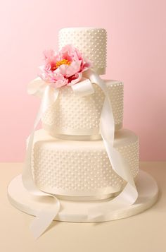 Three tier fondant wedding cake with royal icing dots, satin ribbon and sugar peony.